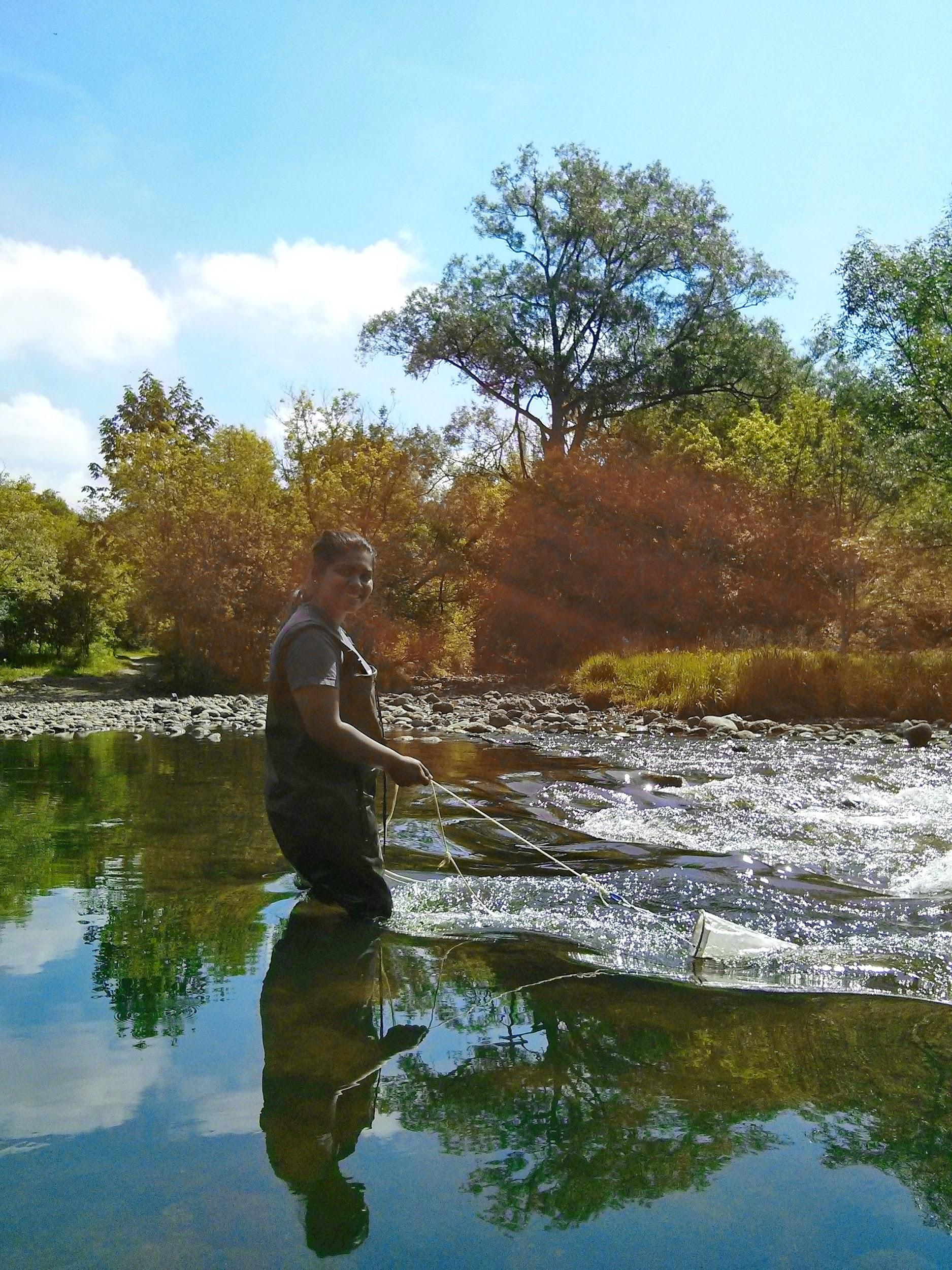 Kareina acquiring a plankton sample with the plankton tow net in flowing water at the Speed River collecting site - Crane Park, Guelph, Ontario.