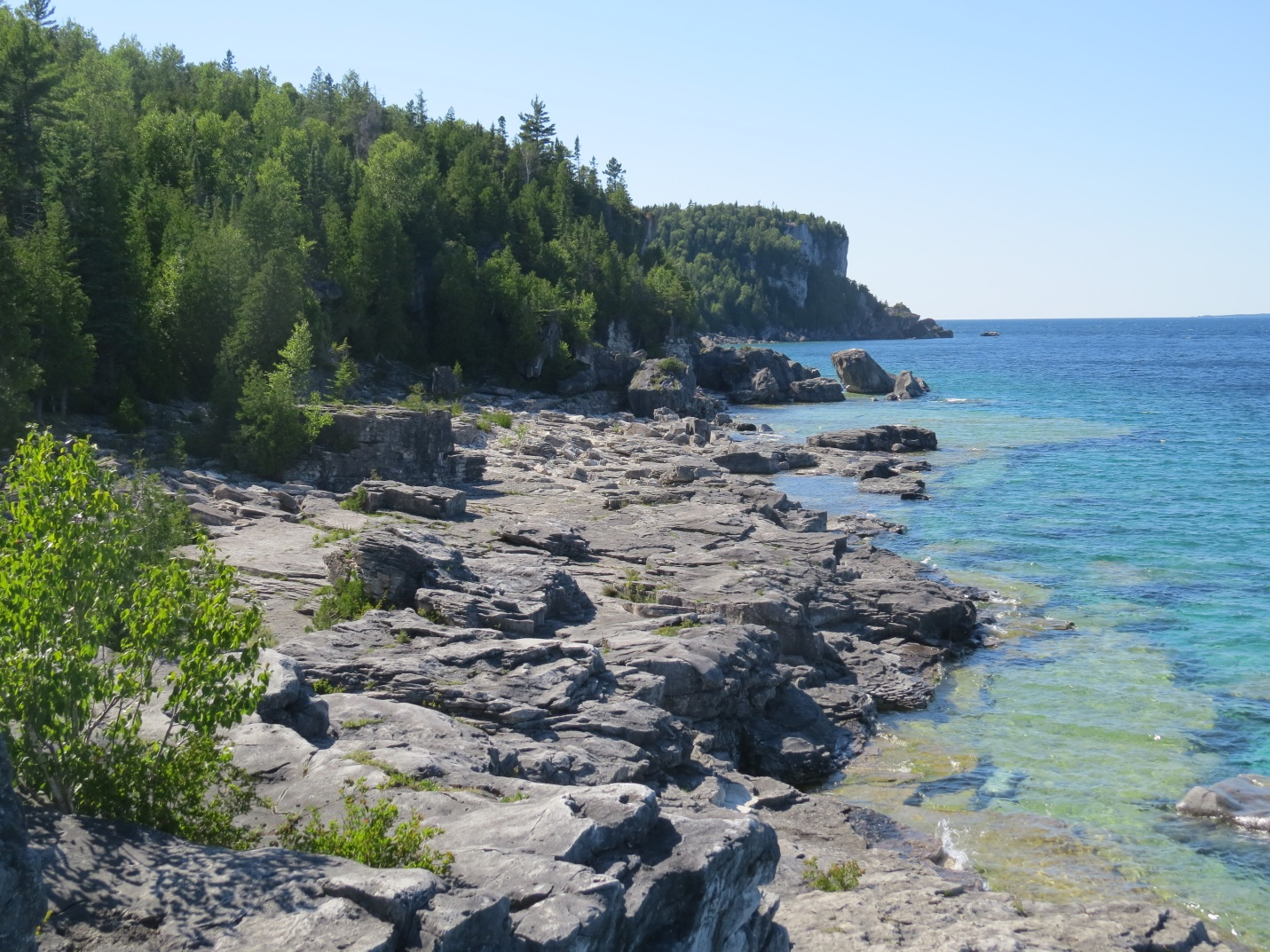 Another photo of the shoreline along Little Cove. The dolomite rock dominates the shoreline and the large cliffs are visible in the background.